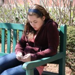 Student sitting in a bench outdoors using a mobile phone